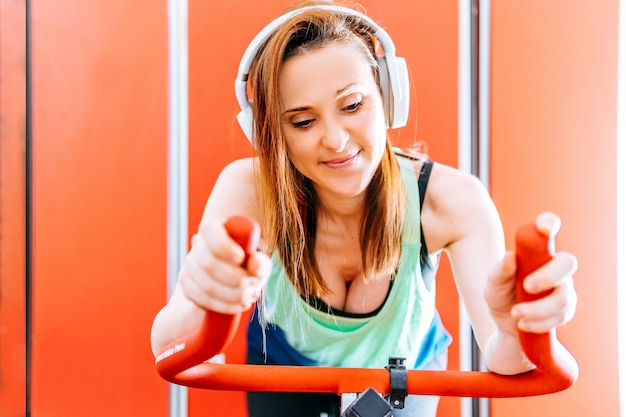 Smiling young beautiful woman doing indoor cycling listening to music with helmets.
