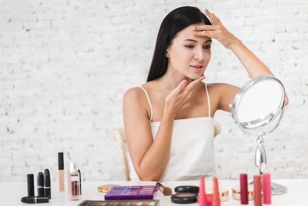 Улыбающаяся молодая красивая женщина со свежей здоровой кожей, глядя в зеркало с косметикой для макияжа, установленной дома