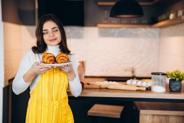 家庭的なキッチンで新鮮なおいしいクロワッサンのプレートを保持しているエプロンと笑顔の若い美しい女性の女の子。魅力的な10代の少女は、自宅でお菓子作りや料理教室を楽しんで楽しんでいます。