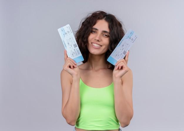 Улыбающаяся молодая красивая женщина, держащая билеты на самолет на изолированной белой стене с копией пространства