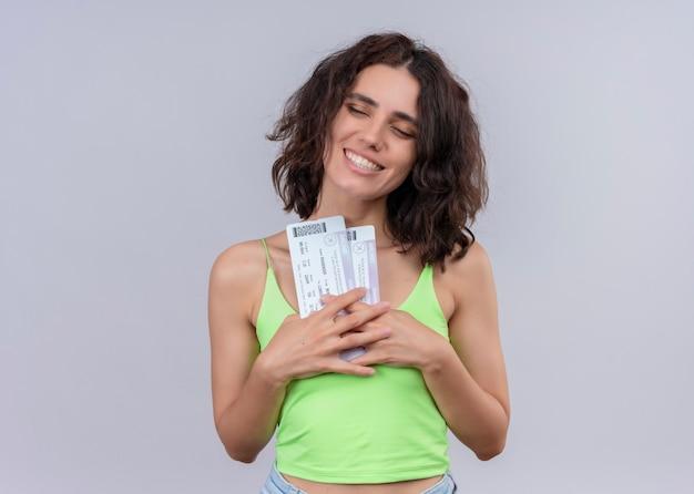 Улыбающаяся молодая красивая женщина, держащая билеты на самолет на изолированной белой стене