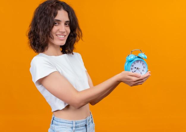 孤立したオレンジ色の壁に目覚まし時計を保持している若い美しい女性を笑顔