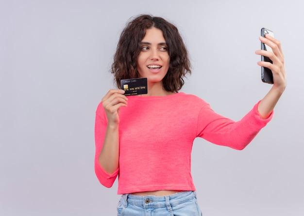 Sorridente giovane bella donna che tiene la carta e prendendo selfie sulla parete bianca isolata