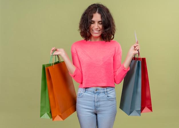 孤立した緑の壁にカートンバッグとカードを保持している若い美しい女性を笑顔