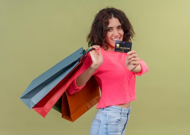 カートンの袋を保持している孤立した緑の壁にカードを伸ばして笑顔の若い美しい女性