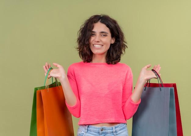 Sorridente giovane bella donna che tiene i sacchetti di cartone sulla parete verde isolata