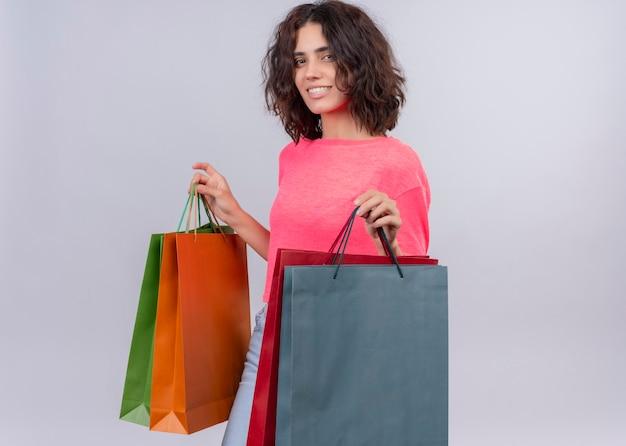 Sorridente giovane bella donna che tiene i sacchetti di cartone sulla parete bianca isolata
