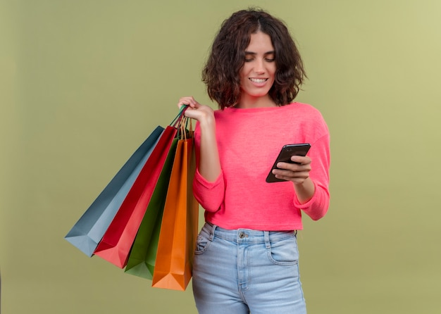 Sorridente giovane bella donna che tiene i sacchetti di cartone e il telefono cellulare sulla parete verde isolata
