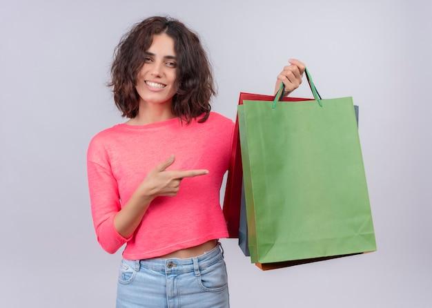 Sorridente giovane bella donna che tiene i sacchetti di cartone e indicandoli sulla parete bianca isolata