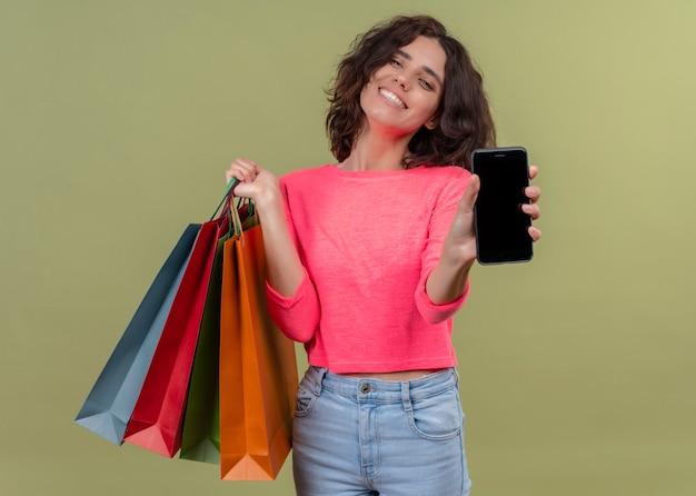 Sorridente giovane bella donna che tiene i sacchetti di cartone e allungando il telefono cellulare sulla parete verde isolata