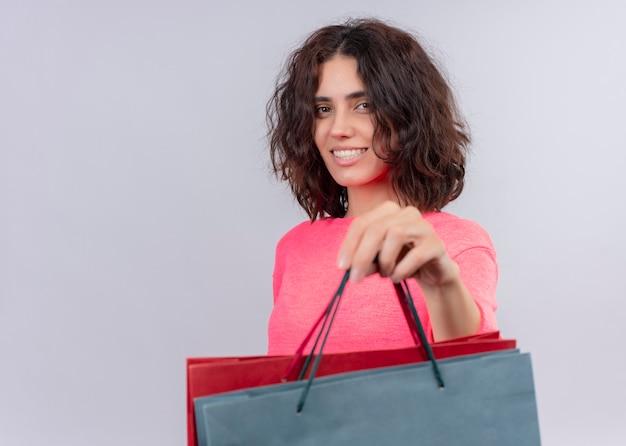 Sorridente giovane bella donna che tiene i sacchetti di cartone e allungandoli sulla parete bianca isolata