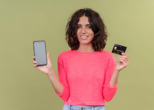 孤立した緑の壁に携帯電話とカードを保持している若い美しい女性を笑顔