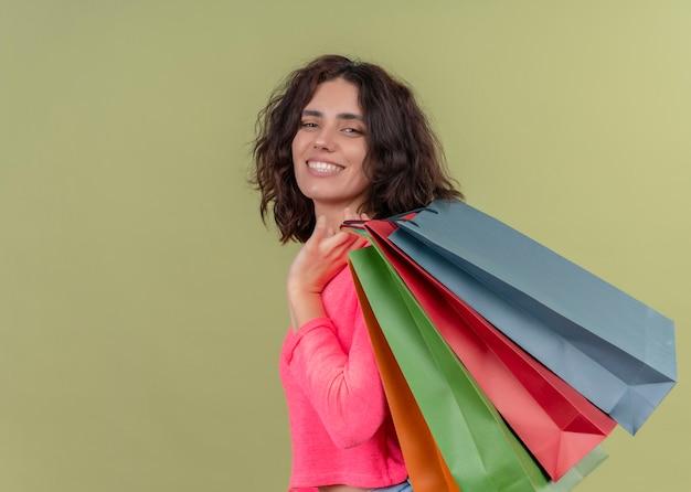 Sorridente giovane bella donna che tiene i sacchetti di carta sulla parete verde isolata con lo spazio della copia