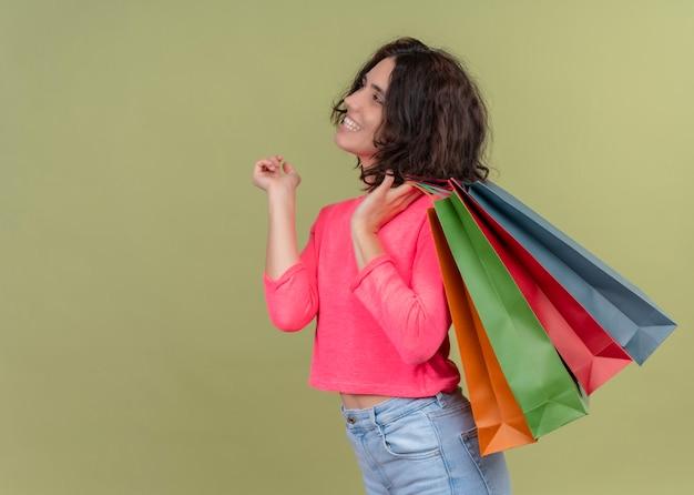 縦断ビューに立って、コピースペースで孤立した緑の壁の左側を見て紙袋を保持している若い美しい女性を笑顔