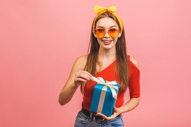 Улыбающаяся молодая красивая женщина держит подарочную коробку
