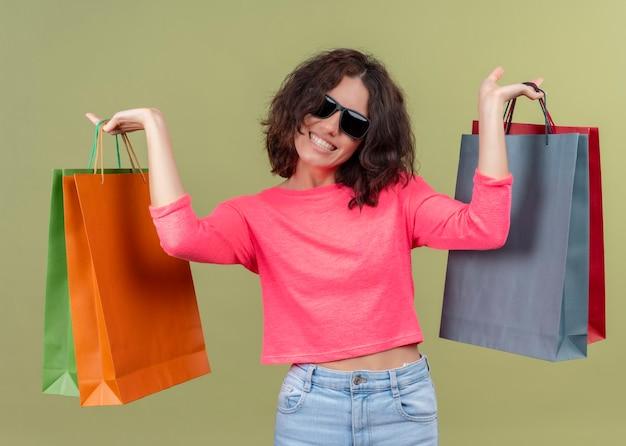 孤立した緑の壁にカートンの袋を上げる笑顔の若い美しい女性