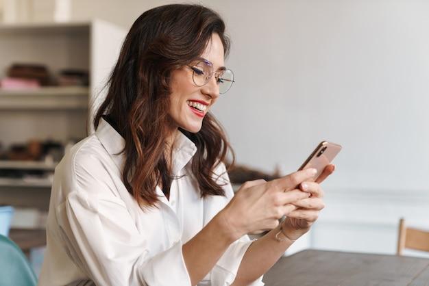 Улыбается молодая красивая женщина с помощью мобильного телефона, сидя за столиком в кафе в помещении