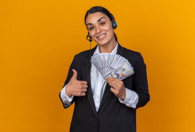 엄지손가락을 보여주는 현금을 들고 헤드셋과 검은 블레이저를 입고 웃는 젊은 아름 다운 여자