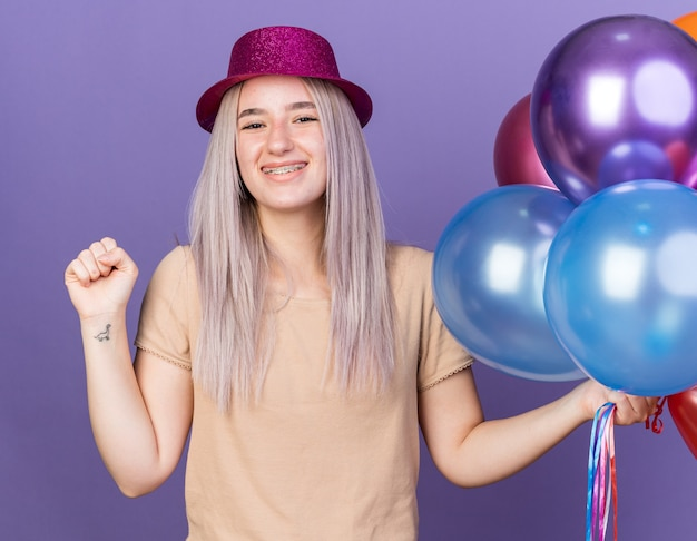 青い壁に分離されたはいジェスチャーを示すバルーンを保持している歯列矯正器とパーティーハットを身に着けている若い美しい女性の笑顔