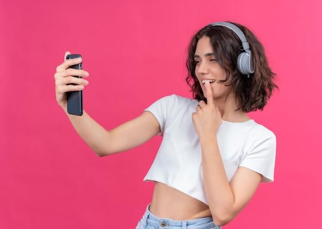 ヘッドフォンを着用し、ピンクの壁の唇に指を置く携帯電話を保持している笑顔の若い美しい女性