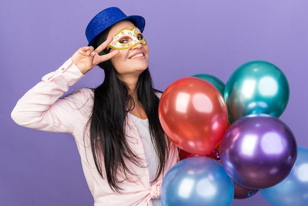 青い壁に分離された平和のジェスチャーを示す風船を保持しているパーティーハットと仮面舞踏会のアイマスクを身に着けている若い美しい女性の笑顔