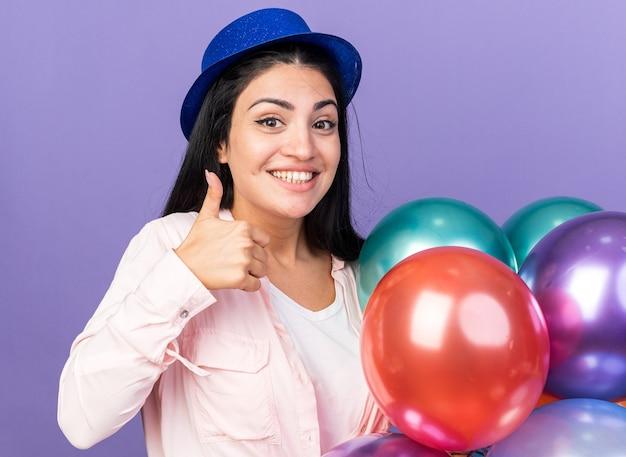 青い壁に分離された親指を示す風船を保持しているパーティーハットを身に着けている若い美しい女性の笑顔