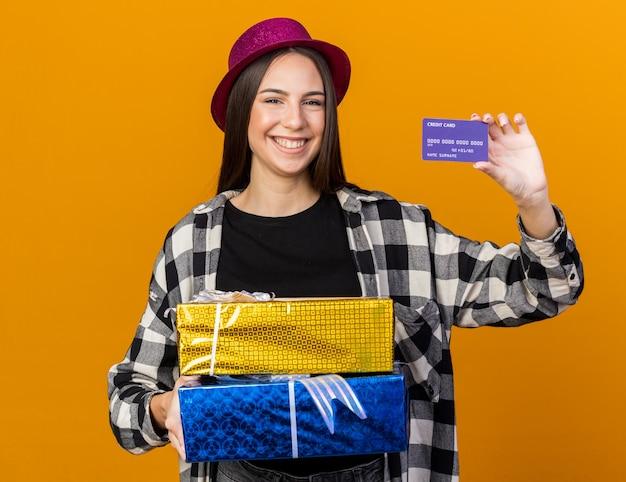 Улыбающаяся молодая красивая женщина в партийной шляпе держит подарочные коробки и кредитную карту, изолированную на оранжевой стене