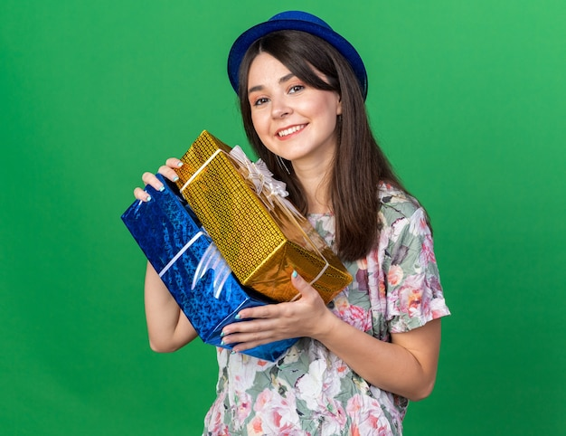 Smiling young beautiful woman wearing party hat holding gift boxes isolated on green wall