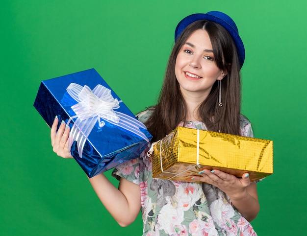 Улыбающаяся молодая красивая женщина в партийной шляпе держит подарочные коробки, изолированные на зеленой стене