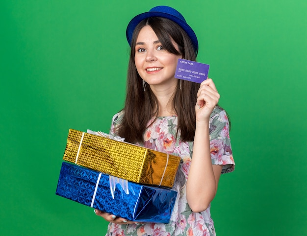 Smiling young beautiful woman wearing party hat holding gift boxes with credit card isolated on green wall