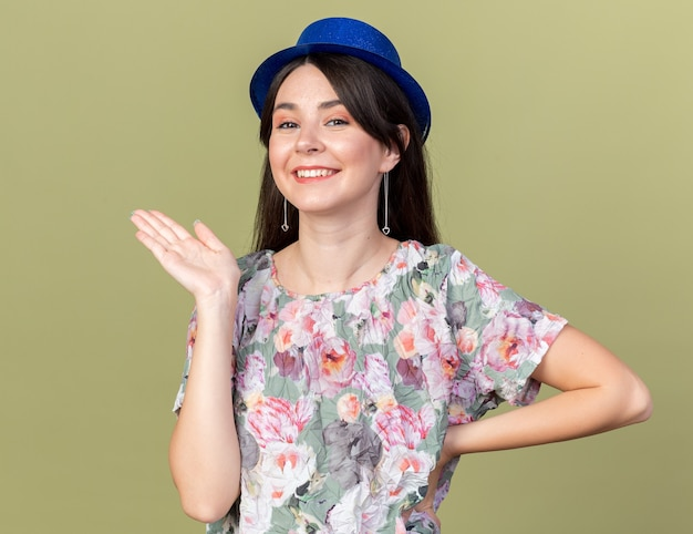 Sorridente giovane bella donna che indossa il cappello da festa punti con la mano a lato isolato su parete verde oliva