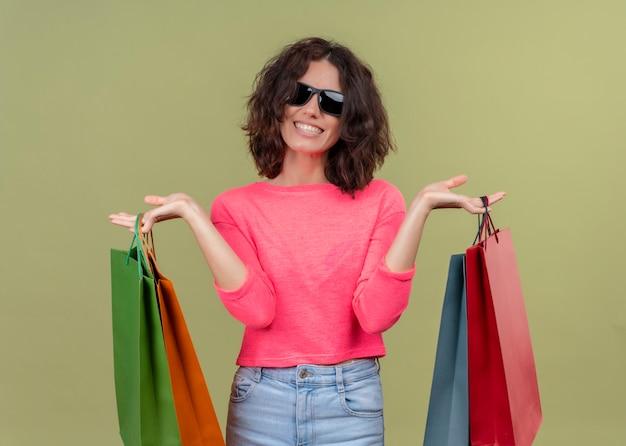 Sorridente giovane bella donna che indossa occhiali da sole e che tiene i sacchetti di cartone sulla parete verde isolata