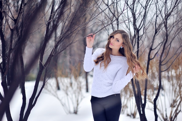 Smiling young beautiful woman in winter forest