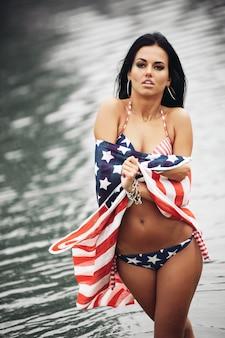 ビーチでアメリカの国旗を持つ若い美しい女性を笑顔