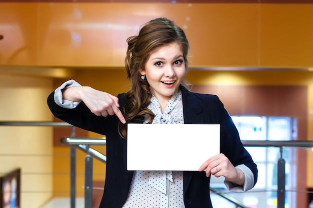 Smiling young beautiful women shows on blank white card