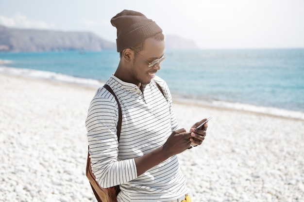 Smiling young black european male tourist in hat and shades using 3g internet on mobile phone on beach, sharing pictures via social media, enjoying happy days during his summer vacations at seaside