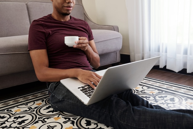 Smiling young black man drinking cup of coffee and checking e-mailson laptop in the morning
