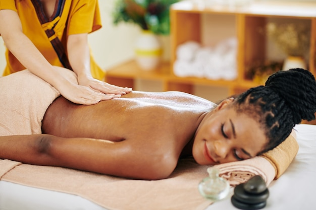Smiling young black woman getting relaxing back massage in beauty salon with aromatic oils