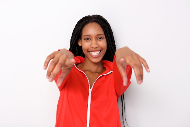 Smiling young black woman pointing fingers on white background