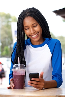 Smiling young black woman using smartphone at cafe