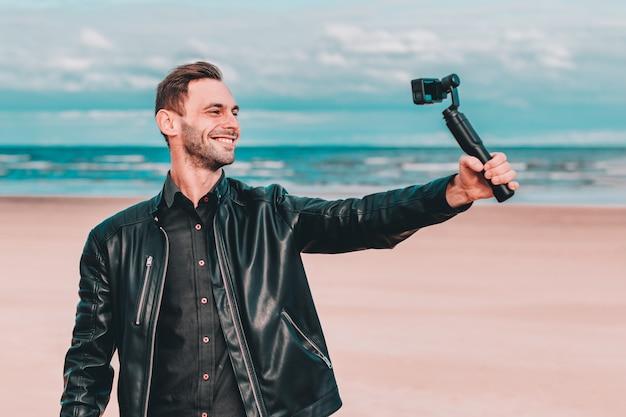 Улыбающийся молодой блоггер делает селфи или транслирует потоковое видео на пляже с помощью камеры действия со стабилизатором камеры.