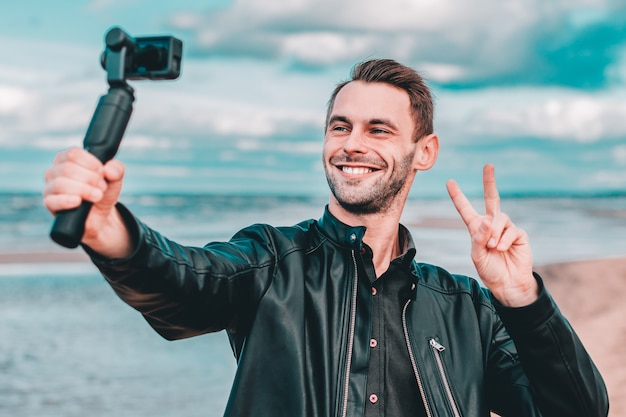 Smiling young blogger making selfie or streaming video at the beach using action camera with gimbal camera stabilizer.