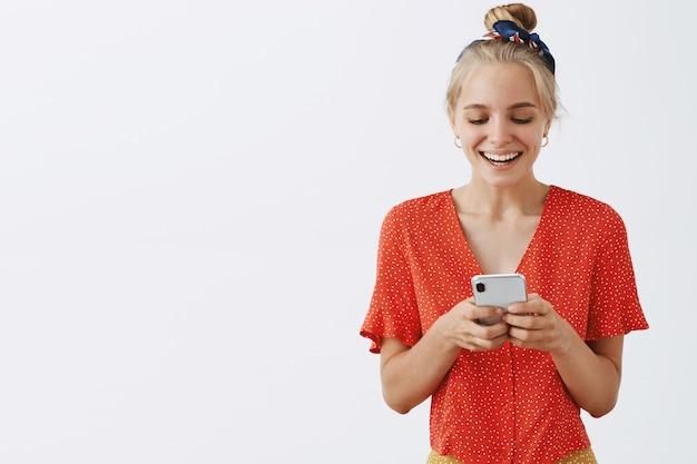 白い壁に向かってポーズをとって笑顔の若いブロンドの女の子