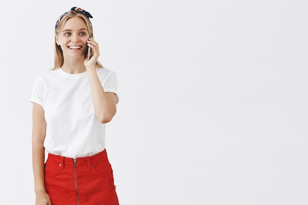 Smiling young blond girl posing against the white wall