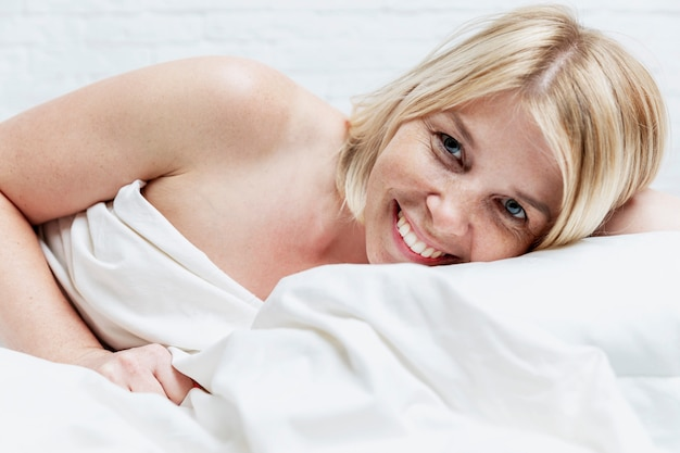 Smiling young blond woman in bed. vigorous early morning and awakening. full sleep and relaxation. close-up.
