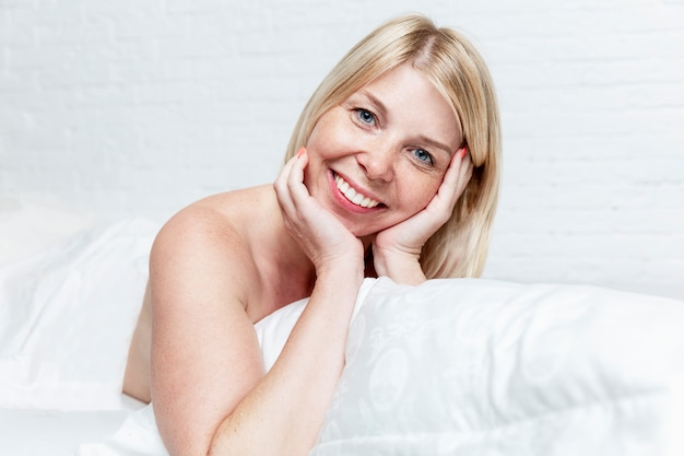 Smiling young blond woman in bed. vigorous early morning and awakening.