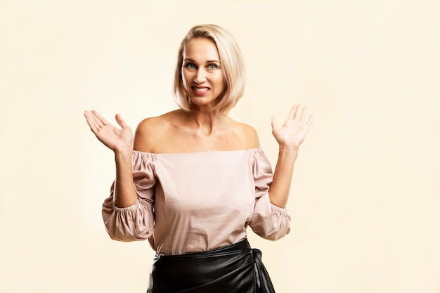 Smiling young blond woman with arms raised up. happiness and positivity. light yellow background.