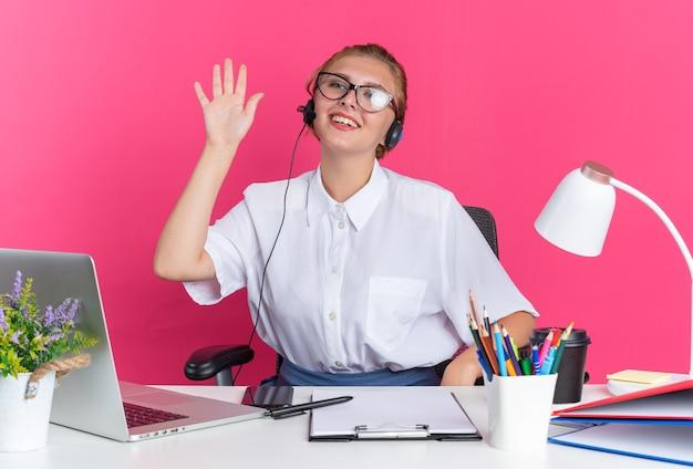 Sorridente ragazza bionda del call center che indossa auricolare e occhiali seduto alla scrivania con strumenti di lavoro guardando il lato facendo ciao gesto isolato sul muro rosa