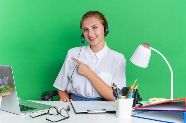 Улыбающаяся молодая блондинка колл-центр девушка в гарнитуре сидит за столом с рабочими инструментами, указывая в сторону