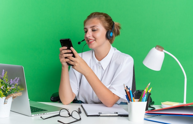 Улыбающаяся молодая блондинка колл-центр девушка в гарнитуре сидит за столом с рабочими инструментами, используя свой мобильный телефон